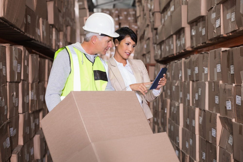 Warehouse worker moving boxes on trolley talking to manager in a large warehouse